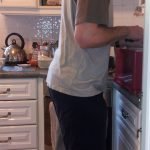 Man stood at kitchen counter in monkey position